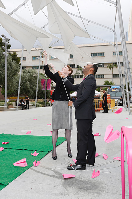 "Rachel Moore, President and CEO of The Music Center and Lucas Rivera, Director, Grand Park hoist the final plane into place during The Music Center's launch of ""Paper Airplane"", the unveiling of a new art installation in Grand Park's Olive Court on Tuesday, September 13, 2016, in Los Angeles, Calif. (Photo by Ryan Miller/Capture Imaging)"